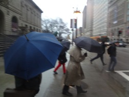 Howard Wolinsky/MEDILL Chicago residents protect themselves from the rainfall with umbrellas.